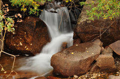 Waterfall cascading down rocks in Rocky Mountains Royalty Free Stock Photo