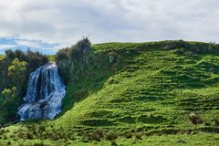 Waterfall cascading from a grassy hillock Royalty Free Stock Photo