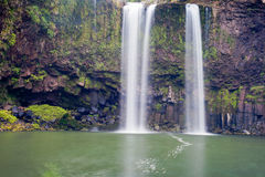 Waterfall cascading over cliff into peaceful pool Royalty Free Stock Photography