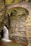 Waterfall cascading over Glen Gorge in Watkins Glen state park. Stone bridge at the top of the falls royalty free stock photography