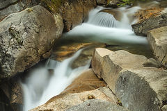 Waterfall cascading over granite rocks near The Basin, New Hamps Royalty Free Stock Photography