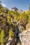 Waterfall amongst pine trees at Paglia Orba in Corsica. Waterfall cascading over rocks into a clear, shallow pool and between pine trees with Paglia Orba Stock Photos