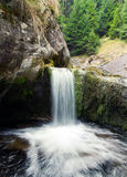 Waterfall cascading into a pool. Scenic mountain waterfall cascading over a rocky ledge into a natural pool below stock image