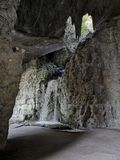 Waterfall in a cavern. Waterfall in a rocky cavern in park Buttes Chaumont in Paris France stock photo
