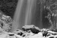 Waterfall in Chartreuse over the icy rock Black and white royalty free stock photography