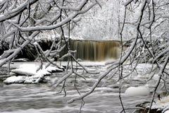 A waterfall churns through the fresh snow Stock Photos