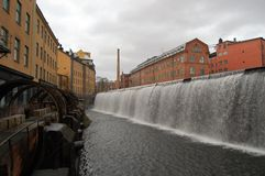 Waterfall in the city. The old industrial landscape in the middle of the town Stock Photography