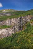 Waterfall and cliff in Geiranger fjord Stock Photos