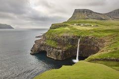Waterfall and cliffs on Vagar. Faroe Islands coastline. Gasaladur