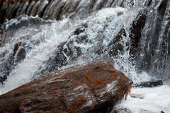 Waterfall close up. Water cascade on moss stones Stock Image