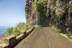 Waterfall on closed old road on the edge of rocky cliff between Ponta do Sol and Jardim do Mar, Madeira island, Portugal. Summer scenery royalty free stock photo