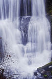 Waterfall closeup with soft flowing water. Closeup of soft cascading waterfall flowing from above stock photos