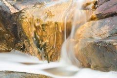 Waterfall and algae-covered rocks Stock Photos