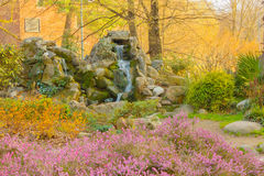 A waterfall in a corner of the flowered park. A waterfall descends gently between the rocks in a pond of a flowered  park Stock Images