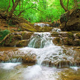 Waterfall in countryside. Scenic view of waterfall in green countryside forest with slow motion blur Royalty Free Stock Photo