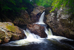 Waterfall in countryside. Scenic view of rocky waterfall in countryside with slow motion blur Stock Photos