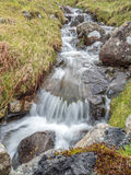 Waterfall in countryside in England. Small waterfall along back road in countryside landscape view in England under cloudy sky Stock Image
