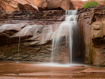 Waterfall in Coyote Gulch Utah. A waterfall pours over the red sandstone in Coyote Gulch, Escalante, Utah Stock Photography