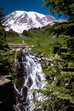 Waterfall crashes down in front of the snow capped Mount Rainier royalty free stock images