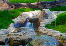 Waterfall on the creek flowing through  green grass Stock Photography