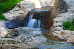 Waterfall on the creek flowing through  green grass Stock Images