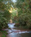 Waterfall to a creek at midday royalty free stock images