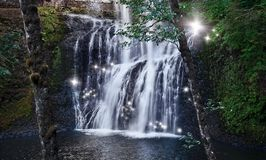 Waterfall with dancing fairy lights in enchanted forest royalty free stock photos