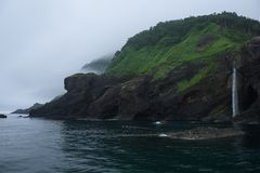 Waterfall dropping from high rocky cliffs into the ocean Sea of Okhotsk around the Shiretoko Peninsula. Hokkaido, Japan Stock Photos