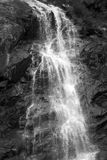 Waterfall drops monochrome scene. Black and white scene particular of a waterfall drops and very dark rocks stock image