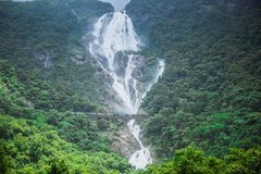 Waterfall Dudh Sagar and passing by the bridge train. India stock images