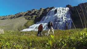 Waterfall Dynjandifoss. Tourist couple at waterfall Dynjandifoss in Westfjords, Iceland stock video