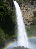 Waterfall in equatorial rainforest, with arched rainbow. Over fall, in Ecuador, South America stock image