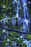 Waterfall with fairies and magical blue moonlight affect. Magical waterfall with fairies and blue misty water cascading over green mossy rocks royalty free stock photography