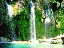 Waterfall falling into blue lagoon in tropical deep forest Royalty Free Stock Photo