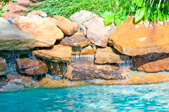 Waterfall falling in a blue swimming pool Royalty Free Stock Photography
