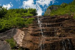 Waterfall falling from slope rocks Royalty Free Stock Photo