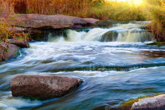 Waterfall on the fast river. Beautiful waterfall on a fast river among stones stock image