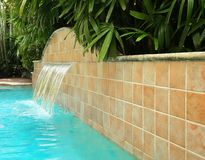 Waterfall feature in a beautiful swimming pool stock images