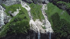 Waterfall flowing down from high mountains on a Sunny day. Top view of the mountain from which the river flows stock photography