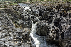 Waterfall Flowing Between the Lava Stones Royalty Free Stock Photos