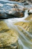 Waterfall flowing over Rocks. A mountain stream creates a small waterfall over mosaic patterned rocks Stock Images