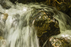 A waterfall flowing over rocks Royalty Free Stock Photo
