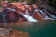 Waterfall Flowing Over Rocks. Waterfall located in the interior of Brazil Flowing Down Rocks into a Blue Pool of Water Stock Image