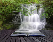 Waterfall flowing over rocks in pages of book