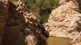 Waterfall flowing on rocks in Oasis Chebika at Sahara desert, Tunisia