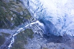 Waterfall flowing under a Glacier Stock Images