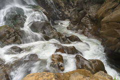 Waterfall flows down the mountain Stock Images