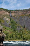 Waterfall flows down from the mountain plateau into the river canyon. Stock Images