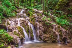 The waterfall flows through the forest. Running water in the forest across the rocks in a green natural environment Royalty Free Stock Images