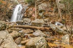 A waterfall flows after a rain in a hidden canyon on a mountain. A waterfall flows into a hidden canyon near a mountain top after heavy rainfall making, forming Royalty Free Stock Image